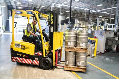 man on forklift carrying kegs