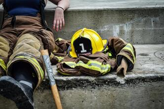 firefighter sitting on step with axe handle, helmet and jacket at her side